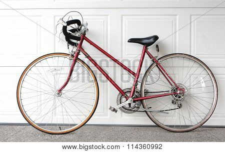 bicycle leaning over a garage door on drive way
