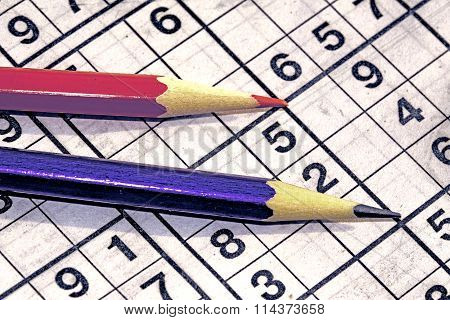 Sudoku game and a ball pen on the table