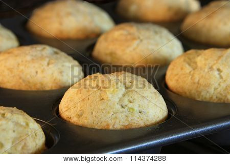 Banana bread muffins baking in a convection oven.