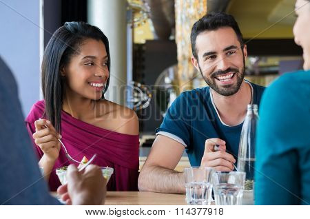 Closeup shot of young woman and man having meal. Happy smiling multiethnic friends eating at restaurant. Shallow depth of field with focus on young friends eating meal.