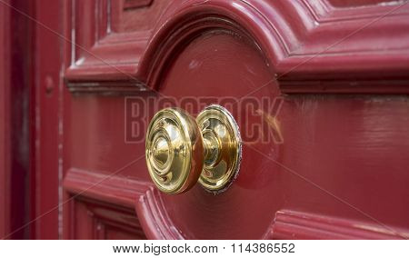 Shiny Brass Doorknob On Red Wooden Entry Door