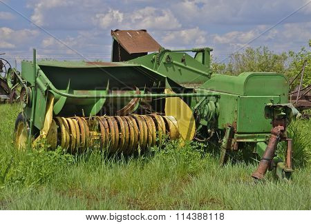 An old green hay baler stands idle