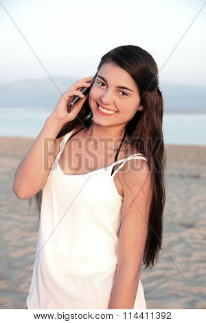 Fresh faced young teenage girl smiling on a cell phone on a beach.