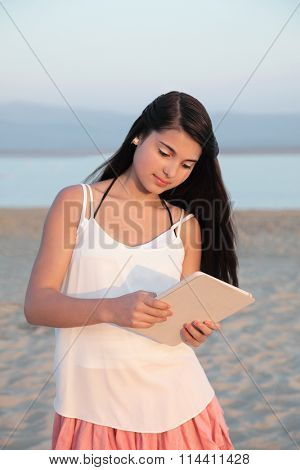 Young caucasian girl browsing on a tablet computer device on a beach in summer.