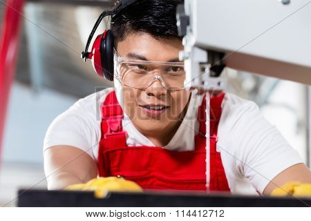 Chinese worker on saw in industrial factory cutting a work piece