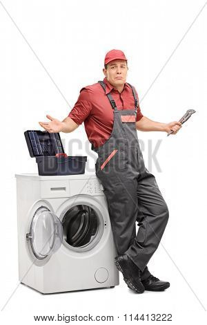 Full length portrait of an uncertain plumber standing next to a washing machine and gesturing with hands isolated on white background