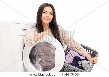 Young cheerful housewife holding a laundry basket and posing next to a washing machine isolated on white background
