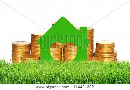 House Symbol Over Golden Coins In Green Grass Isolated On White
