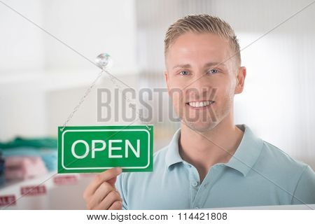 Male Owner Holding Open Sign In Clothing Store