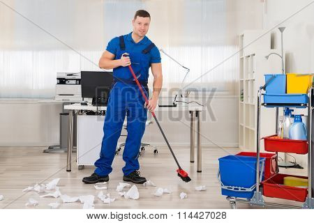 Janitor Cleaning Floor With Broom In Office