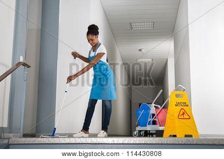 Woman Mopping Corridor