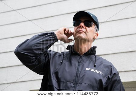 Confident Security Guard Listening To Earpiece Against Building