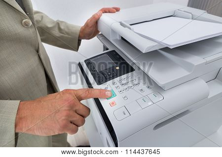 Midsection Of Businessman Pressing Printer's Button