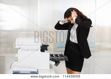 Irritated Businesswoman Looking At Printer Machine At Office