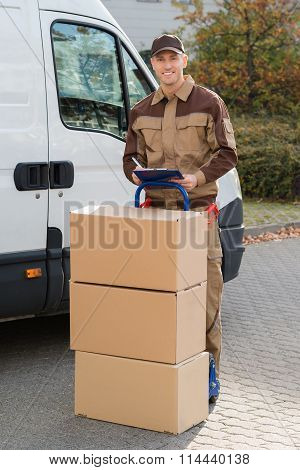 Confident Delivery Man With Parcels And Clipboard On Street