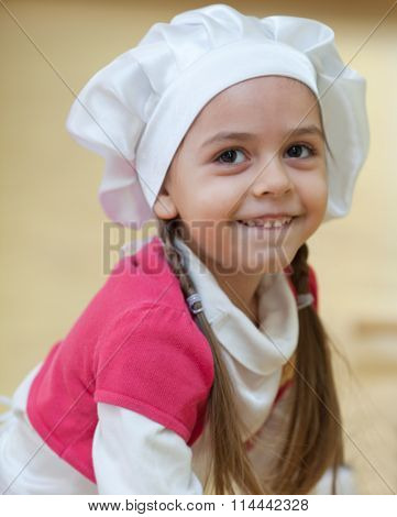 Little girl wearing chef's hat close up