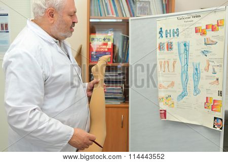 RUSSIA, MOSCOW - AUG 31, 2015: doctor phlebologist and informational poster about varicose veins in office of  multidisciplinary Clinic Center Endosurgery and Lithotripsy (CELT)