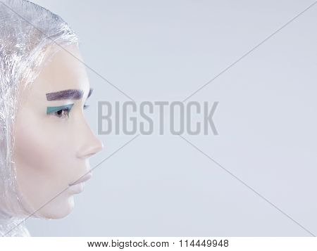 Profile of misterous pretty woman wrapped in cellophane looking forward standing on light grey backg