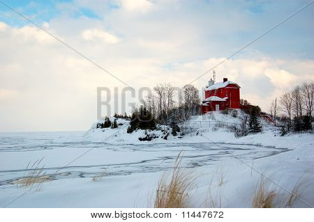 Red Lighthouse On Frozen Shoreline