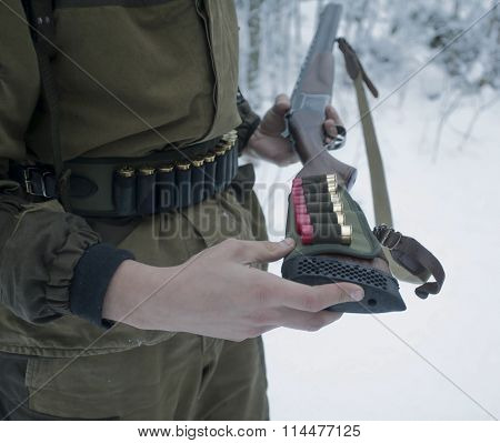 Gun With Cartridge Belt In Hands Of Hunter