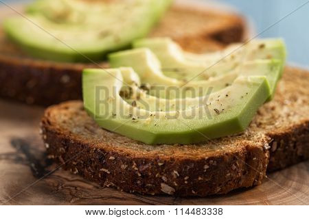 toasted rye bread with sliced avocado and herbs