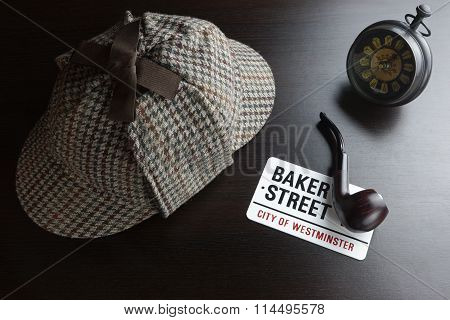Deerstalker Hat Vintage Clock Sign Baker Street And Smoking Pipe On The Black Table Background. Overhead View. Investigation Concept.