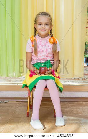 Girl Sitting On A Chair With An Apple In His Hand On A Matinee In Kindergarten
