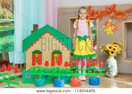 A Girl Stands At The Scenery House On Matinee In Kindergarten