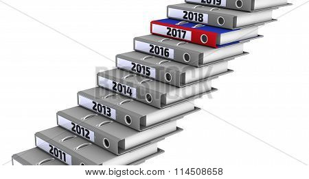 Folders stacked in the form of steps, marked the years 2011-2018. Focus for 2017