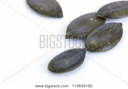 Peeled pumpkin seeds. Closeup. Isolated over white.
