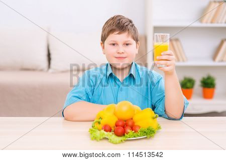 Chubby kid with juice and veggies.
