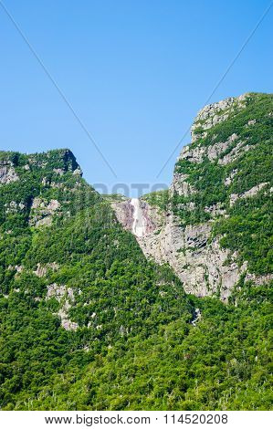 Steep Cliffs Covered In Trees With Distant Waterfall Under Blue Sky