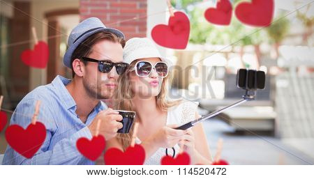Cute couple taking a selfie with selfie stick against hearts hanging on a line