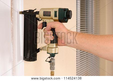 Carpenter using nail gun to complete door framing trim