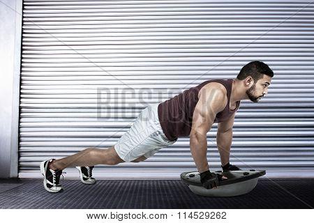 Muscular man doing bosu push ups against shutter in gym
