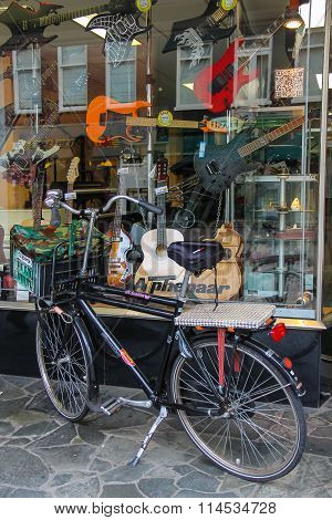 Parked Bicycle In Front Of Shop Window With Different Types Of Guitars, Haarlem, The Netherlands