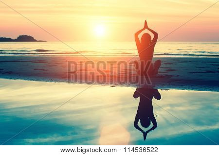 Silhouette meditation girl on the background of the stunning sea and sunset. Yoga, fitness and healthy lifestyle. Woman doing meditation near the ocean.