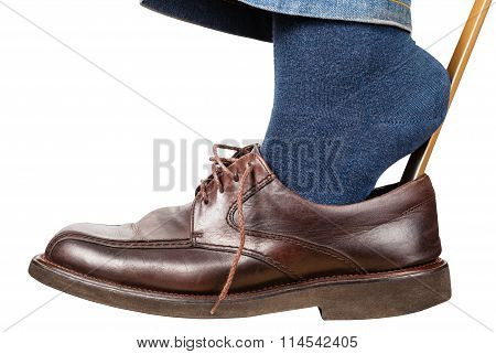 Man Puts On Brown Shoes Using Shoe Horn Isolated