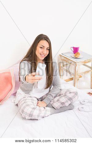 Teenage girl in pajamas in bed taking a selfie on smartphone