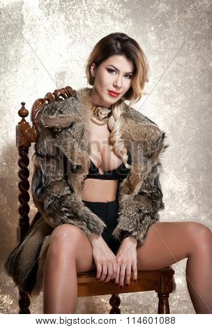 Attractive and sexy blonde woman with black lingerie and fur coat posing provocatively sitting