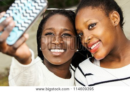 Two African Teens Taking Selfie With Smart Phone.