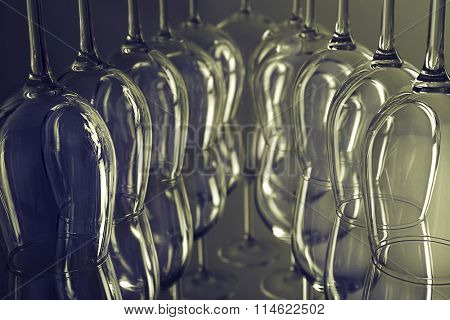 Wine glasses in a row upside down on grey background