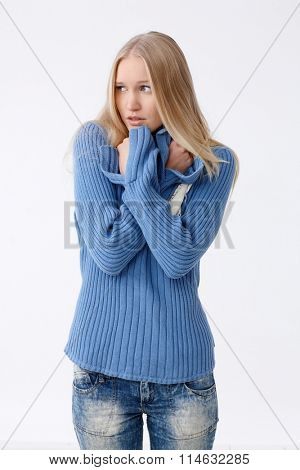 Young blonde woman freezing or frightened, folding arms defensively, looking away.