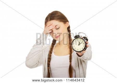 Tired teenage woman with alarmclock.