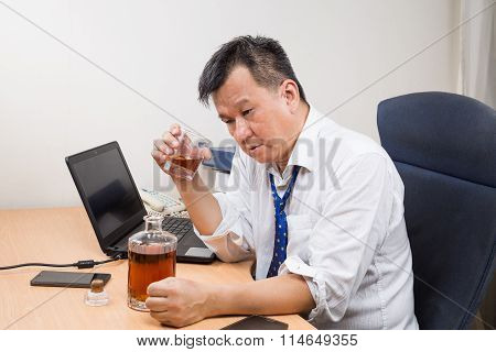 Frustrated And Stressful Asian Manager Drinking Hard Liquor In Office