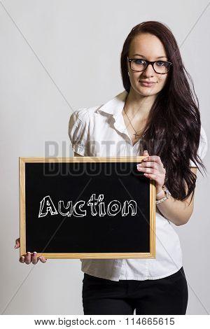 Auction - Young Businesswoman Holding Chalkboard
