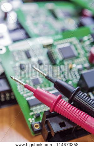 Laboratory Components And Staff. Pins Of Digital Multimeter In Front Of Printed Circuit  Boards With