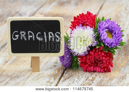 Gracias (thank you in Spanish) card with bouquet of colorful aster flowers on rustic woo