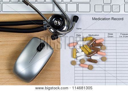 Patient medication record form with stethoscope pills computer keyboard and mouse on wooden desktop. Mouse and keyboard are nonfunctional no name brand items for display on desktops. poster