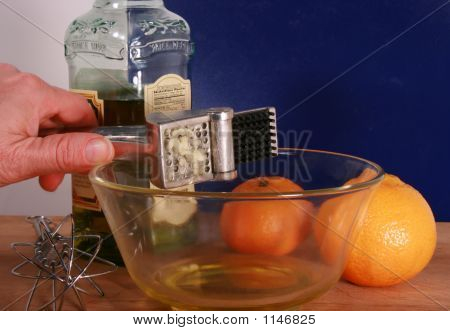 Garlic Press In Glass Bowl With Oranges And Bottle Of Olive Oil In Background
